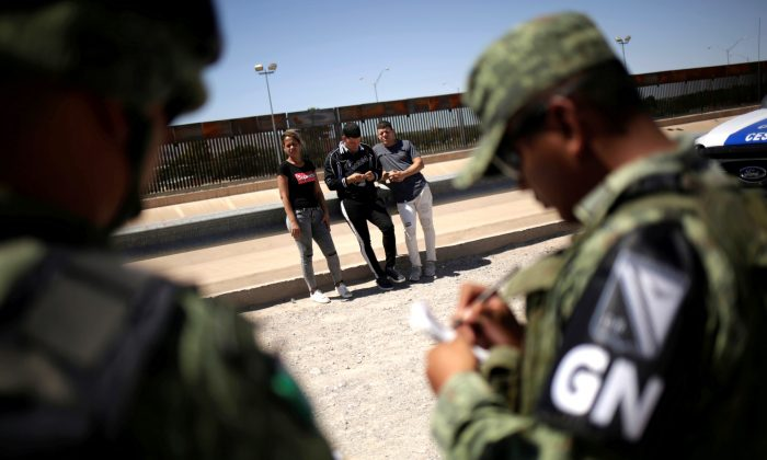 Members of Mexico's National Guard detain Cuban migrants after they were trying to cross illegally the border between the U.S. and Mexico, in Ciudad Juarez, Mexico June 21, 2019. (Reuters/Jose Luis Gonzalez)