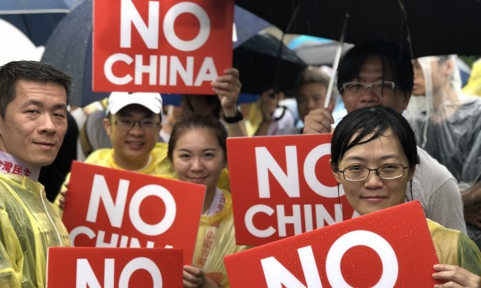 Protesters hold up signs at a rally against pro-Beijing Taiwanese media in Taipei, Taiwan, on June 23, 2019. (Chen Pochou/The Epoch Times)