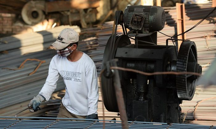A man works at a private steel workshop in the Dong Anh district on the outskirts of Hanoi, Vietnman, on Nov. 14, 2014. (Hoang Dinh Nam/AFP/Getty Images)