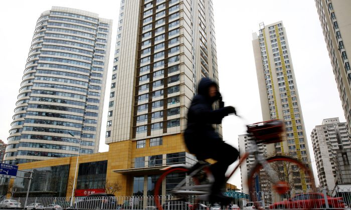 A woman cycles past a building in Tianjin, China, on Dec. 21, 2018. (Thomas Peter/Reuters)