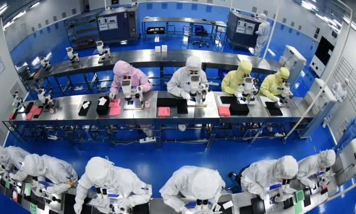 Employees work on a production line manufacturing camera lenses for cellphones at a factory in Lianyungang, Jiangsu Province, China on April 30, 2019. (China Daily via Reuters)