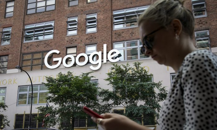 A woman looks at her smartphone as she walks past Google Building 8510 at 85 10th Ave  in New York City, on June 3, 2019. (Drew Angerer/Getty Images)