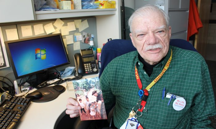 Bob Hall holds a photograph of himself playing with children in a village in Vietnam during his time as a Marine. Hall was one of the earliest patients to be interviewed for the My Life, My Story program. Now he is one of the program's writers. (Bram Sable-Smith for NPR)