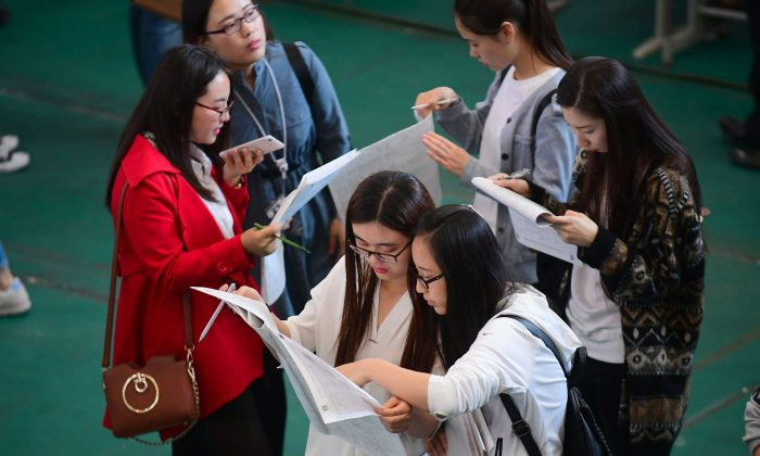 Young adults looking at postings at a job fair at Shenyang Aerospace University in Shenyang, in China's northeast Liaoning Province on May 13, 2017. (China OUT/STR/AFP/Getty Images)