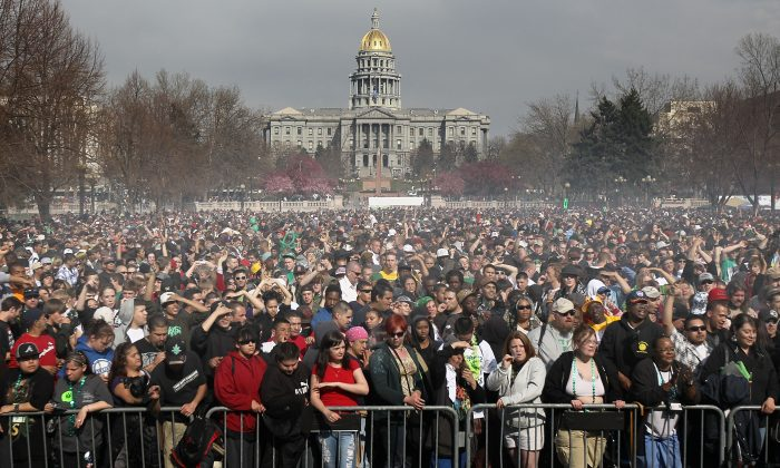 """Marijuana smoke rises from a smoking crowd April 20, 2010 at a pro-pot """"4/20"""" celebration in front of the state capitol building in Denver, Col. (John Moore/Getty Images)"""
