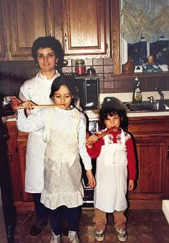 young italian girls taste tomato sauce in kitchen with mother