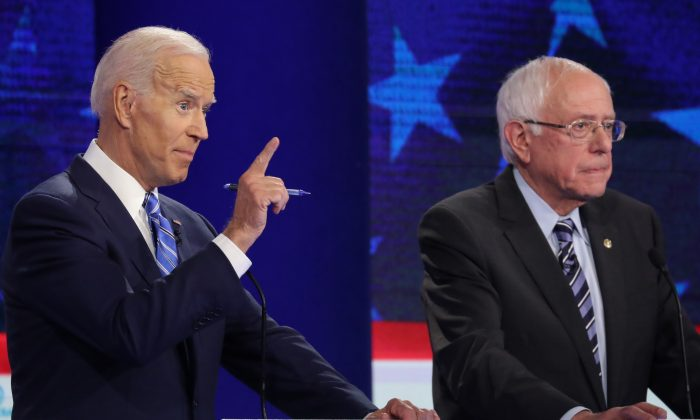Democratic presidential candidate former Vice President Joe Biden speaks as Sen. Bernie Sanders (I-Vt.) looks on during the second night of the first Democratic presidential debate in Miami, Florida, on June 27, 2019. A field of 20 Democratic presidential candidates was split into two groups of 10 for the first debate of the 2020 election, taking place over two nights at Knight Concert Hall of the Adrienne Arsht Center for the Performing Arts of Miami-Dade County, hosted by NBC News, MSNBC, and Telemundo. (Drew Angerer/Getty Images)