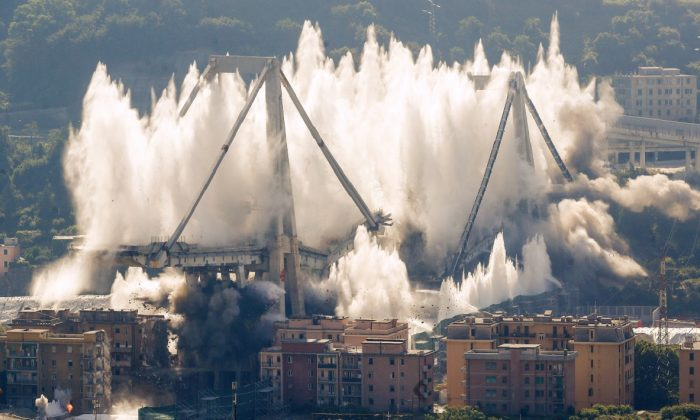 A cloud of dust rises as the remaining spans of the Morandi bridge are demolished in a planned explosion, in Genoa, Italy, on June 28, 2019. (Antonio Calanni/AP Photo)