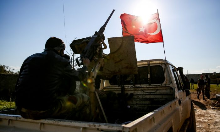 A Syrian fighter of the Turkish-backed Hamza Division mans a turret mounted in the back of a pickup truck flying a Turkish flag at a position in the village of Ulashli near the frontline in the northeast of Aleppo province on March 7, 2019. (NAZEER AL-KHATIB/AFP/Getty Images)
