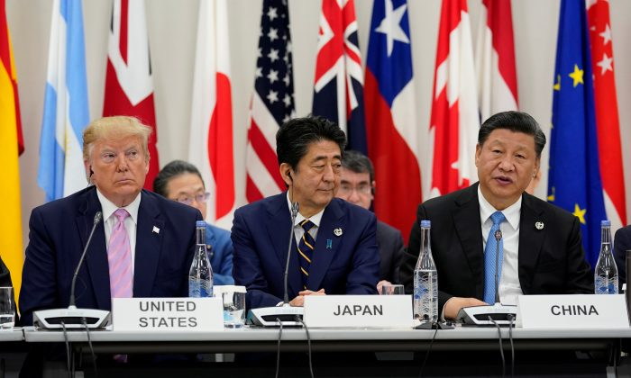 Japan's Prime Minister Shinzo Abe is flanked by U.S. President Donald Trump and Chinese leader Xi Jinping during a meeting at the G20 leaders summit in Osaka, Japan, on June 28, 2019. (Kevin Lamarque/Reuters)
