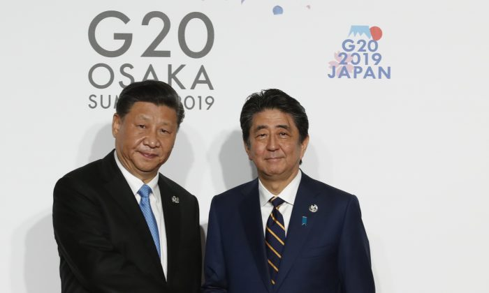 Chinese leader Xi Jinping welcomed by Japanese Prime Minister Shinzo Abe for a family photo session on the first day of the G20 summit in Osaka, Japan on June 28, 2019. (Kim Kyung-Hoon-Pool/Getty Images)