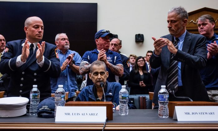 Retired Fire Department of New York Lieutenant and 9/11 responder Michael O'Connell, left, FealGood Foundation co-founder John Feal, center, and former Daily Show Host Jon Stewart, right, applaud following testimony from Retired New York Police Department detective and 9/11 responder Luis Alvarez during a House Judiciary Committee hearing on reauthorization of the September 11th Victim Compensation Fund on Capitol Hill in Washington on June 11, 2019. (Zach Gibson/Getty Images)
