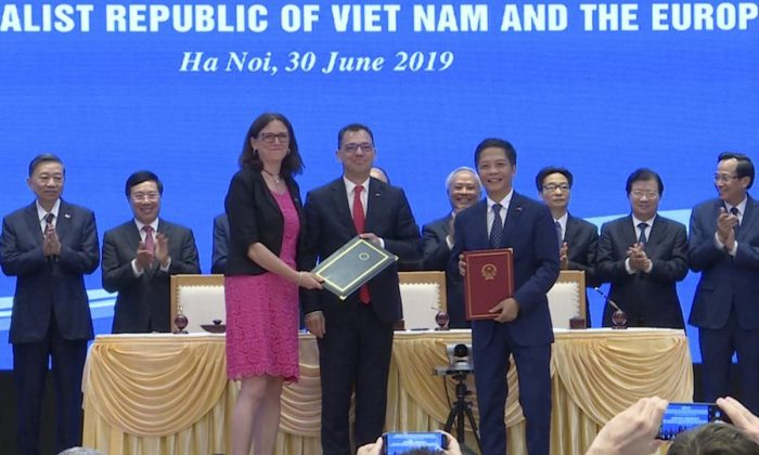 EU Commissioner for Trade Cecilia Malmstrom, front (L), and Vietnamese Trade Minister Tran Tuan Anh, front (R), stand together as they exchange documents in Hanoi, on June 30, 2019. (AP Photo)