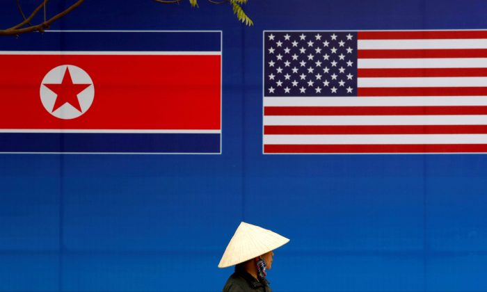 A person walks past a banner showing North Korean and U.S. flags ahead of the North Korea-U.S. summit in Hanoi, Vietnam, on Feb. 25, 2019. (Kim Kyung-Hoon/Reuters)