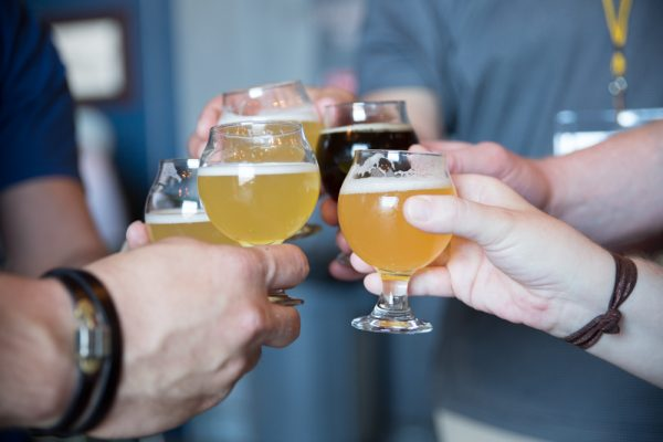 friends hold four glasses of beer samples