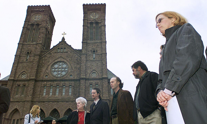 In this May 9, 2002, file photo, Phyllis Hutnak, right, prepares to speak to the media outside the offices of the Diocese of Providence in Providence, R.I. Hutnak said she was seduced by the late Monsignor Louis Dunn of St. Thomas Church in Providence when she was a teenager. Dunn was listed by the Roman Catholic Diocese of Providence on July 1, 2019, as one of several members of clergy, religious order priests, and deacons who have been credibly accused of sexually abusing children. Dunn died in 2001. (AP Photo/Stew Milne)
