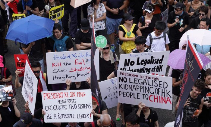 Protesters hold up different signs while participating in a march in Hong Kong on July 1, 2019. (Yu Gang/The Epoch Times)