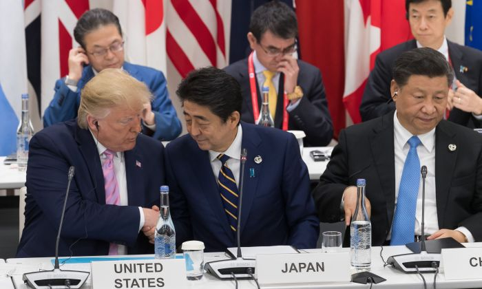 US President Donald Trump (L) shakes hands with Japan's Prime Minister Shinzo Abe (C) as they sit beside China's President Xi Jinping as they attend a meeting on the digital economy at the G20 Summit in Osaka on June 28, 2019. (JACQUES WITT/AFP/Getty Images)