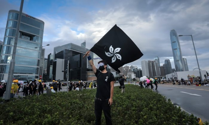 """A protester waves a """"Black Bauhinia"""" flag as others set up barricades at Lung Wo road outside the Legislative Council in Hong Kong before the flag raising ceremony to mark the 22nd anniversary of handover to China early on July 1, 2019. (Vivek Prakash/AFP/Getty Images)"""