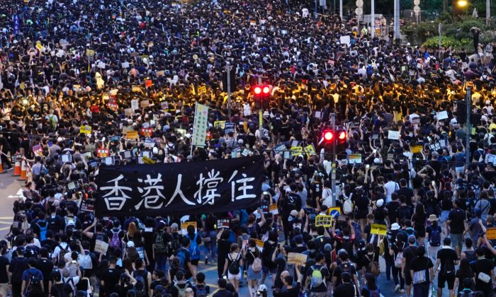 """Protesters holding a sign that reads """"Hongkongers keep going"""" during the annual march in Hong Kong on July 1, 2019. (Yu Gang/The Epoch Times)"""