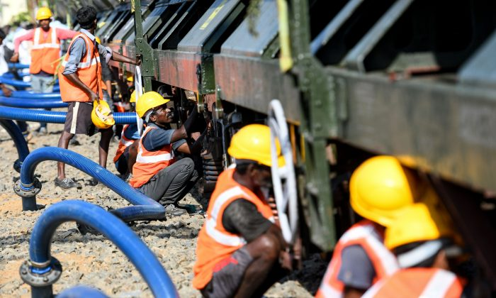 Indian labourers connect pipes to collect water from a special train of 50 wagons carrying litres of water at Villivakkam railway station in Chennai on July 12, 2019.(Arun Sankar/AFP/Getty Images)