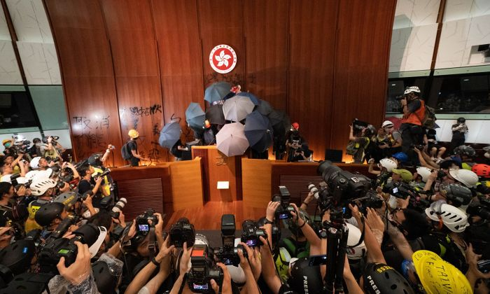 Protesters gather at the podium after they broke into the Legislature Council building in Hong Kong on July 1, 2019. (Li Yi/The Epoch Times)