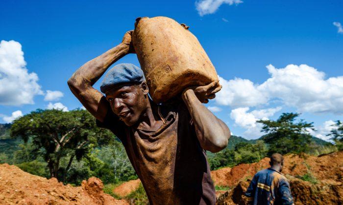 A miner carries a load of ore at Manzou Farm, owned by Grace Mugabe, wife of former Zimbabwean President Robert Mugabe, in Mazowe, Zimbabwe on April 5, 2018. (Jekesai Njikizana/AFP/Getty Images)