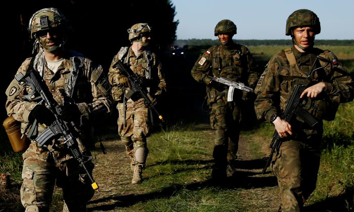 Poland's 6th Airborne Brigade soldiers walk with U.S. 82nd Airborne Division soldiers during the NATO allies' Anakonda 16 exercise near Torun, Poland, on June 7, 2016. (Kacper Pempel/Reuters)