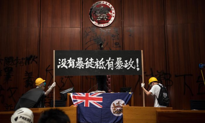 "Protesters hold a banner with the words ""No Rioters, Only Tyranny"" at the Legislative Council to protest against the extradition bill in Hong Kong on July 1, 2019. (Billy H.C. Kwok/Getty Images)"