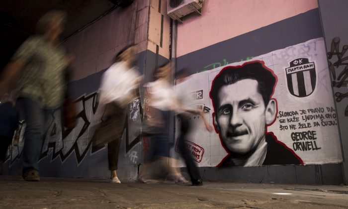 "People walk past a mural painted by an artist of the Grobarski Trash Romantizam (GTR) group, depicting British novelist George Orwell with the reading ""Freedom is the right to tell people what they do not want to hear,"" in Belgrade on May 8, 2018. OLIVER BUNIC/AFP/Getty Images"