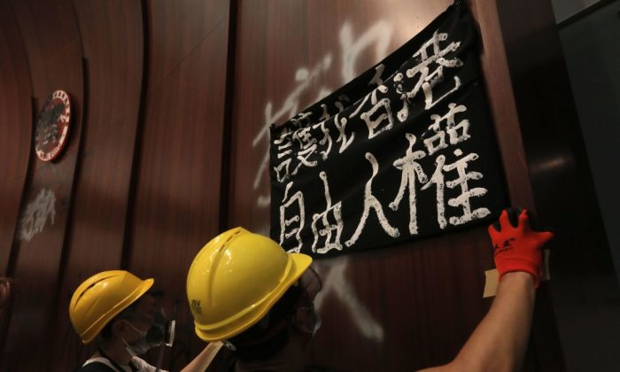 "Protesters put up a sign reading ""Protect my Hong Kong; Freedom, human rights,"" after breaking into the parliament chambers of the government headquarters in Hong Kong on July 1, 2019. (VIVEK PRAKASH/AFP/Getty Images)"