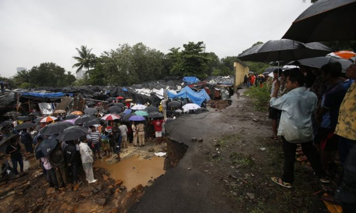 Rescuers and others gather at the spot after heavy rainfall caused a wall to collapse onto shanties, in Mumbai, India on July 2, 2019. (Rafiq Maqbool/Photo AP)
