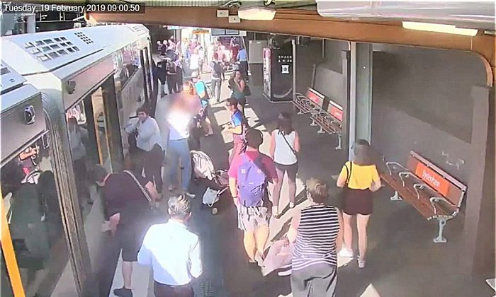 People look down between a train and platform, as a boy fell through train gap, in Sydney, Australia on Feb. 19, 2019, in this video grab obtained by Reuters on July 2, 2019. (Sydney Trains/via Reuters)