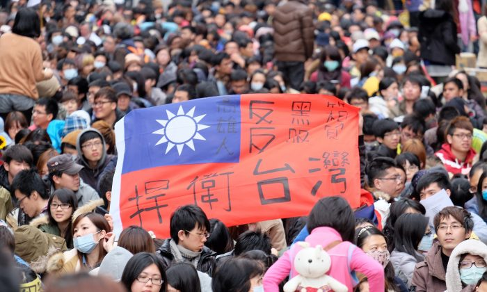 """Protesters displays a Taiwan flag with the words """"protect Taiwan"""" on it during ongoing protests by thousands of people outside the parliament in Taipei, Taiwan, on March 22, 2014. (Sam Yeh/AFP/Getty Images)"""