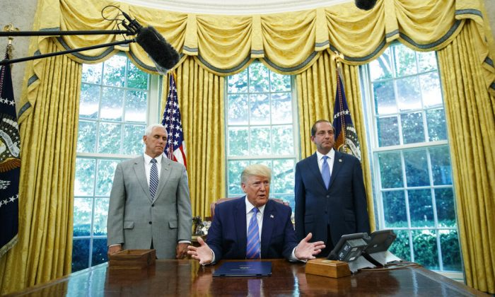 President Donald Trump, joined by Vice President Mike Pence, left, and Secretary of Health and Human Services Alex Azar, right, speaks during a signing ceremony in the Oval Office of the White House in Washington, Monday, July 1, 2019. The president signed a $4.6 billion aid package to help the federal government cope with the surge of Central American immigrants at the U.S.-Mexico border. (AP Photo/Carolyn Kaster)