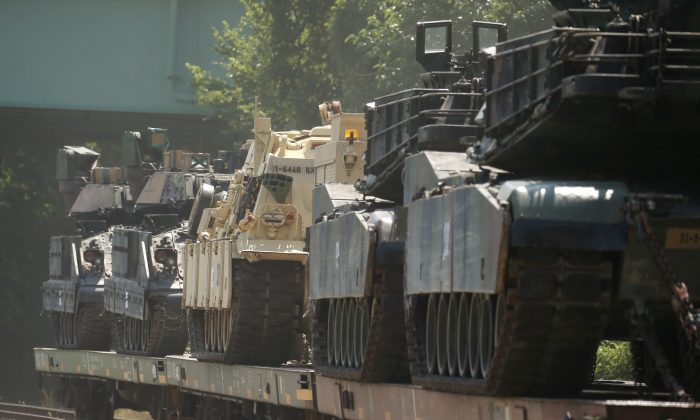 M1 Abrams tanks and other armored vehicles sit atop flat cars in a rail yard after President Donald Trump said tanks and other military hardware would be part of Fourth of July displays of military prowess in Washington, on July 2, 2019. (Leah Millis/Reuters)