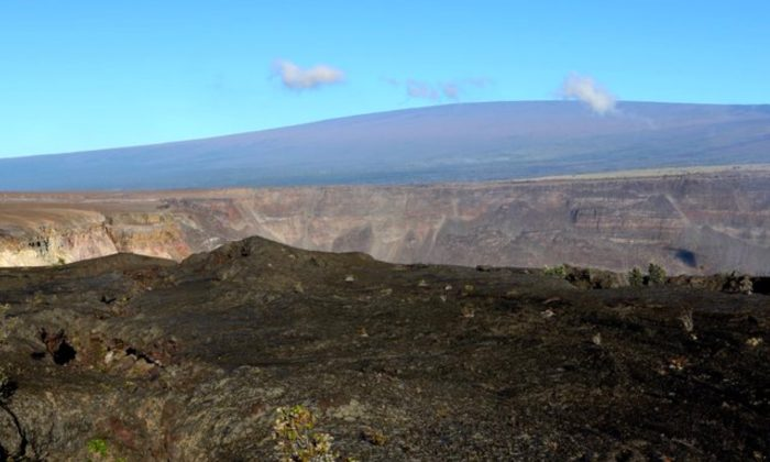 Hawaii's Mauna Loa volcano, background, towers over the summit crater of Kilauea volcano in Hawaii Volcanoes National Park on the Big Island on April 25, 2019. (Caleb Jones/Photo AP)