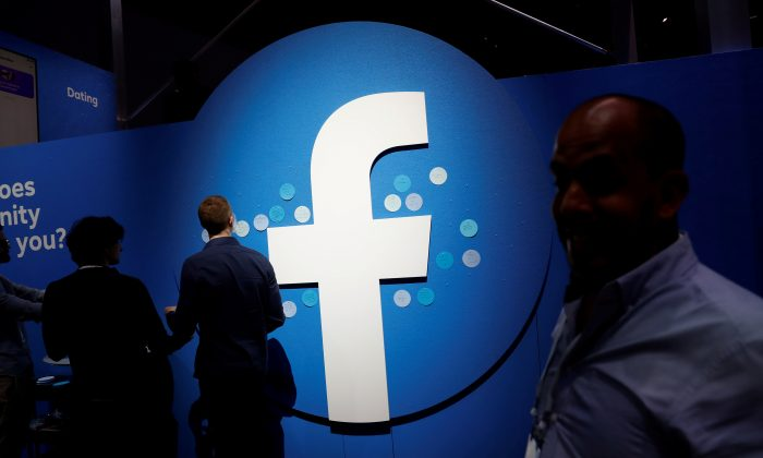 Attendees walk past a Facebook logo during Facebook Inc's F8 developers conference in San Jose, Calif., on April 30, 2019. (Stephen Lam/File Photo via Reuters)