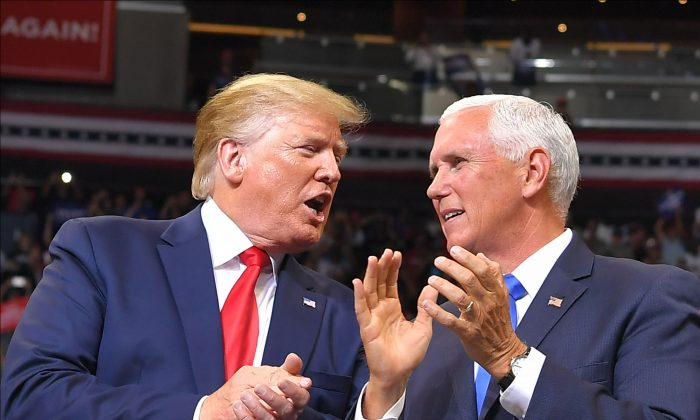 Vice President Mike Pence speaks with President Donald Trump at a rally to officially launch the Trump 2020 campaign, at the Amway Center in Orlando, Fla., on June 18, 2019. MANDEL NGAN/AFP/Getty Images
