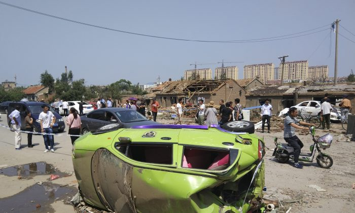 Residents past by an overturned car in the aftermath of a tornado in Kaiyuan in northeastern China's Liaoning Province on July 4, 2019. A tornado blew through the city in northeast China, damaging factories and buildings, killing some people and injuring others, state media reported. (Chinatopix Via AP)