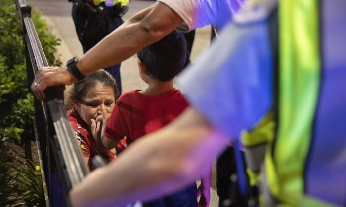 Chicago Police Department (CPD) officers stand guard while a woman relieves her son who had panicked after reports of stabbings and threatening injuries after the 4th of July celebrations at Chicago's Navy Pier. (Amr Alfiky/Photo via AP)