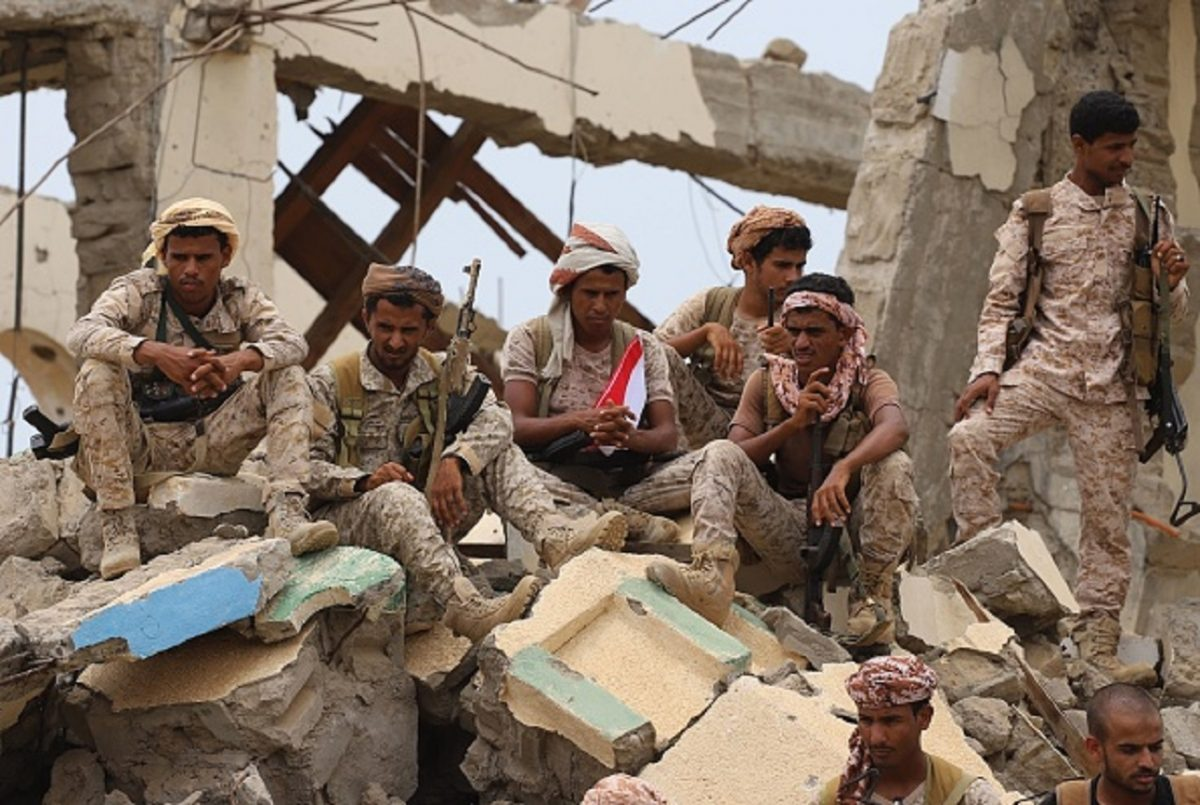 Saudi-backed Yemeni fighters gather above debris of a building while watching the launch