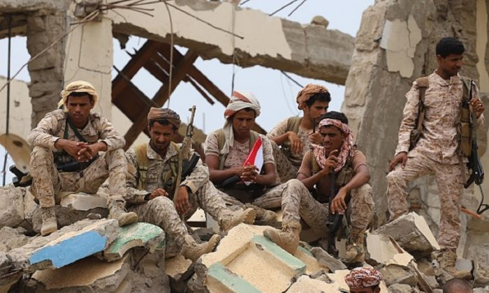 Saudi-backed Yemeni fighters gather above debris of a building while watching the launch by Saudi Development and Reconstruction Program for Yemen (SDRPY) of multi-million dollar aid projects in the area of Yemen's northern coastal town of Midi, located in conflict-ridden Hajjah governorate near the border with Saudi Arabia, on April 22, 2019.       (AFP/Getty Images)