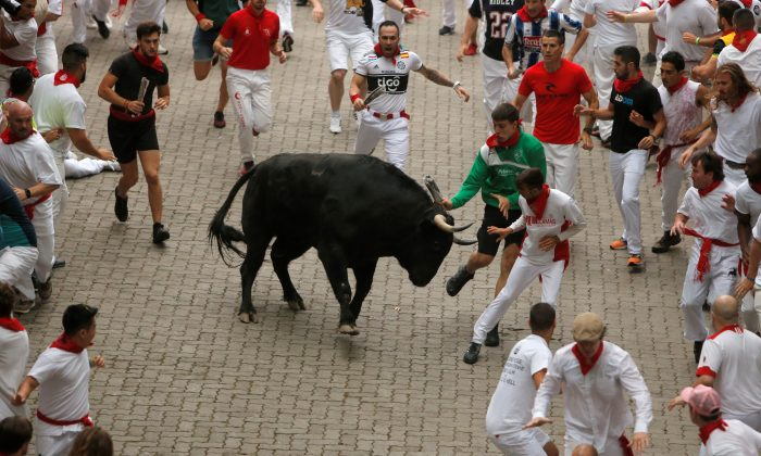 Revellers attempt to dodge a bull during the first running of the bulls at the San Fermin festival in Pamplona, Spain, July 7, 2019. (Jon Nazca/Reuters)