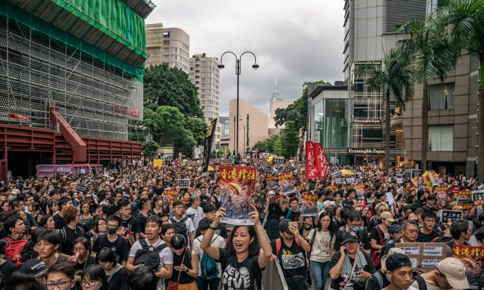 Protesters hold placards and shout slogans as they take part in a rally on a street on July 7, 2019 in Hong Kong, China. Over 230,000 people rallied at Kowloon on Sunday as pro-democracy demonstrators have continued on the streets of Hong Kong for the past month, calling for the complete withdrawal of a controversial extradition bill. (Anthony Kwan/Getty Images)
