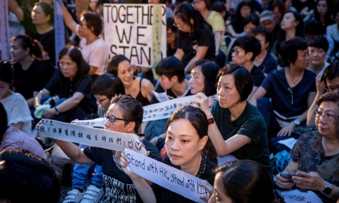 "People hold up banners and posters during a ""mums protest"" against alleged police brutality and the proposed extradition treaty in Hong Kong on June 5, 2019. (Chris McGrath/Getty Images)"