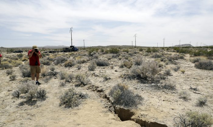 A visitor takes a photo of a crack on the ground following recent earthquakes outside of Ridgecrest, Calif. on July 7, 2019.  AP Photo/Marcio Jose Sanchez