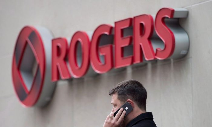 A man speaks on a mobile phone outside Rogers Communications Inc.'s annual general meeting of shareholders in Toronto on April 22, 2014. Rogers Wireless says customers may experience intermittent issues making or receiving wireless voice calls. (Darren Calabrese/The Canadian Press)