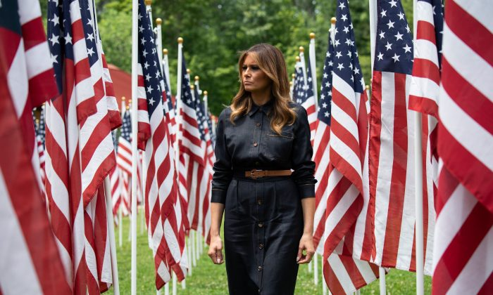 US First Lady Melania Trump walks through 453 American flags, each representing a child in foster care in Cabell County, West Virginia, many due to the opioid epidemic, at Ritter Park in Huntington, West Virginia, July 8, 2019. (SAUL LOEB/AFP/Getty Images)