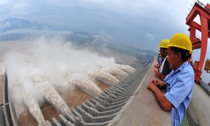 Workers watch the water released from the Three Gorges Dam, a gigantic hydropower project on the Yangtze River in Yichang, central China's Hubei Province on July 24, 2012. (STR/AFP/GettyImages)